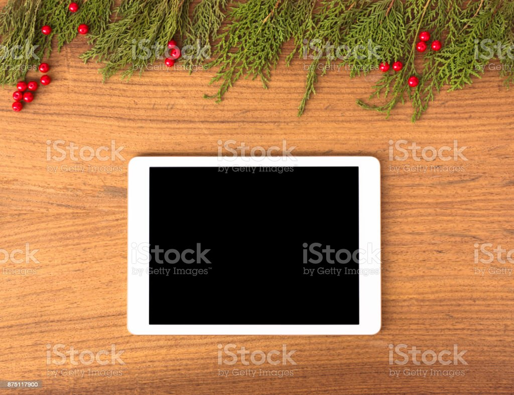 tablet display on table with isolated white screen for mockup in Christmas time. Christmas tree, gifts, decorations in background. stock photo