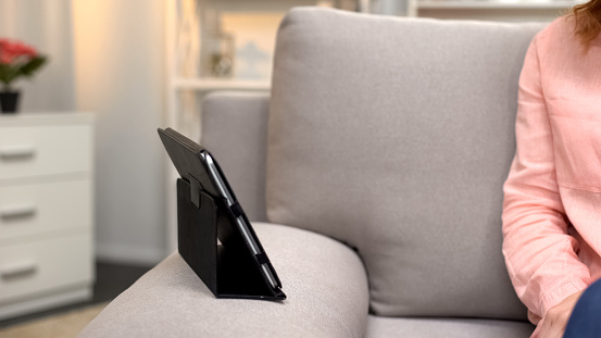 Tablet in case on sofa front of woman, gadget communication, modern technology