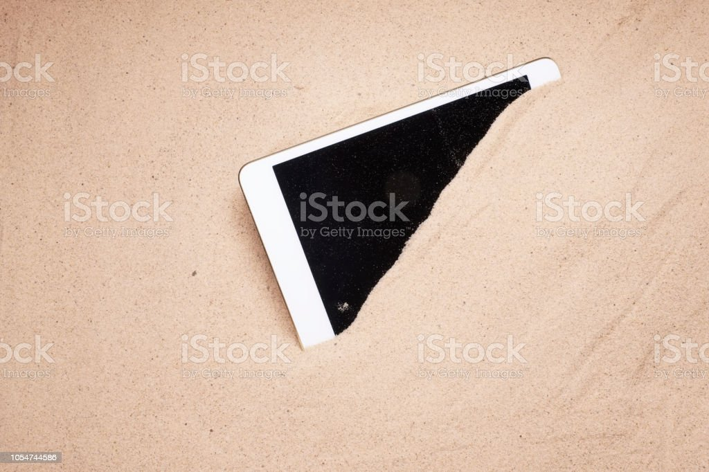 Tablet Mobile Screen Display Covered In Sand At The Beach