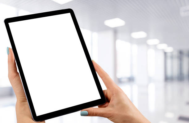 Tablet mockup in woman hand with business centre background. Modern tablet computer mock up with blank white screen. Empty space for text. Copy space. Isolated white screen. Clipping path stock photo