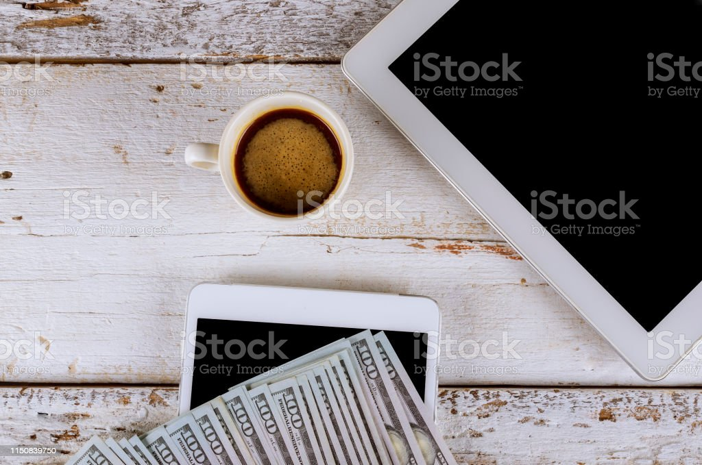 Tablet mockup on work desk with cup of coffee and US dollar banknote...