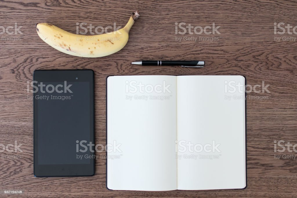Tablet, notebook, pen and a banana on a wooden table. Fake news concept stock photo