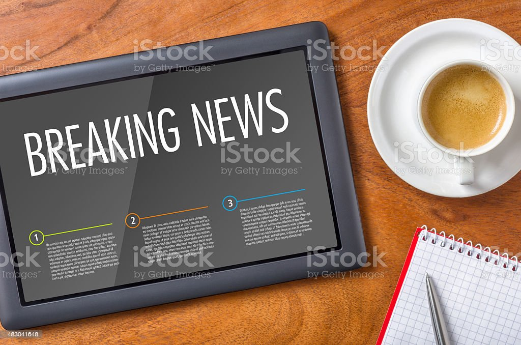 Tablet on a wooden desk - Breaking News stock photo