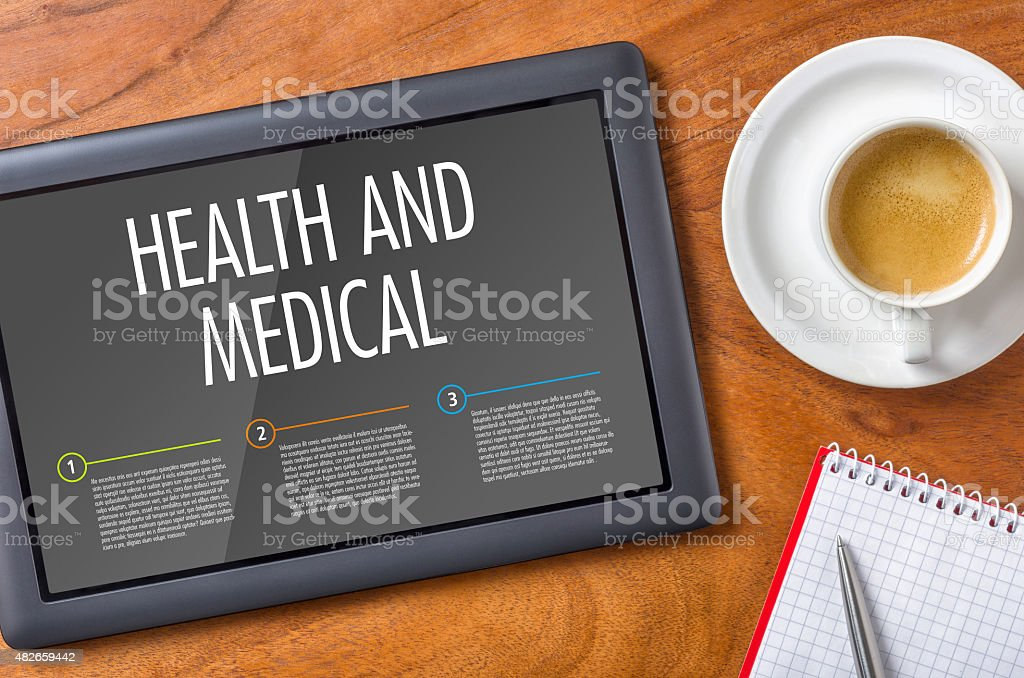 Tablet on a wooden desk - Health and Medical stock photo