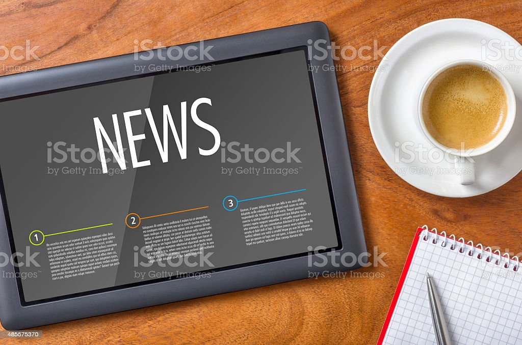 Tablet on a wooden desk - News stock photo