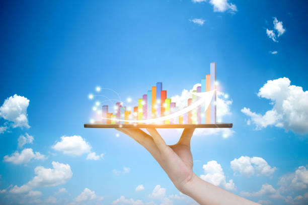 Tablet on hand growth progress graph analysis or success business concept Sky background stock photo