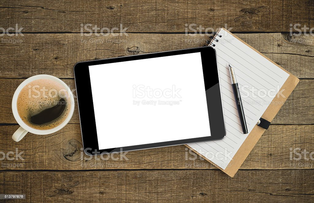 tablet on wood desk on top view stock photo