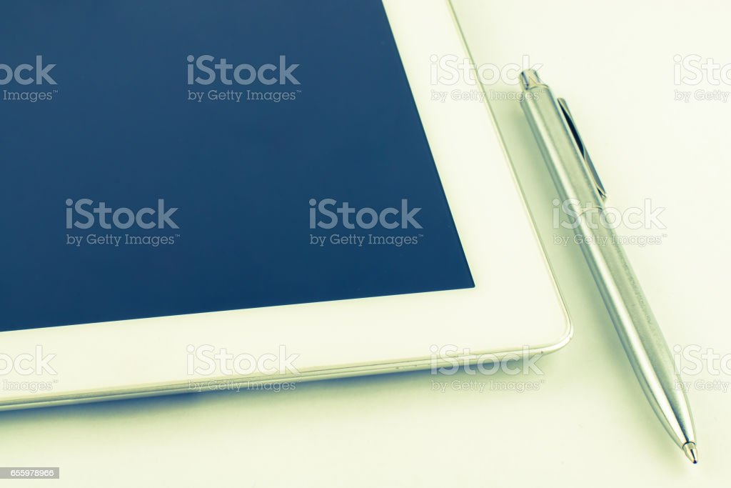 Tablet PC and a modern metal pen on a white background. stock photo