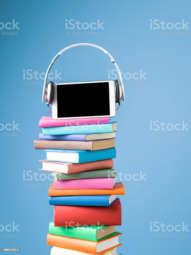 Tablet PC And Headphones On Top Of Multicolored Hardcover Books stock photo