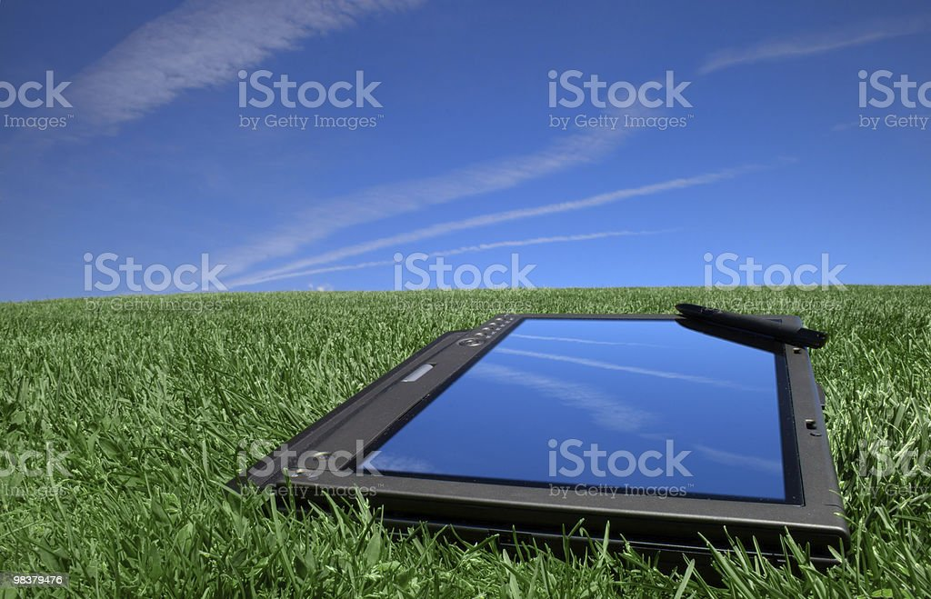 Tablet PC on green grass under blue sky royalty-free stock photo
