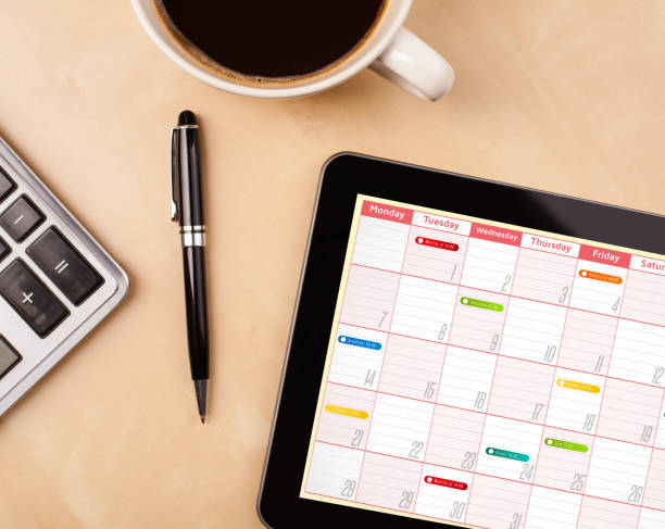 Tablet pc showing calendar on screen with a cup of coffee on a desk stock photo