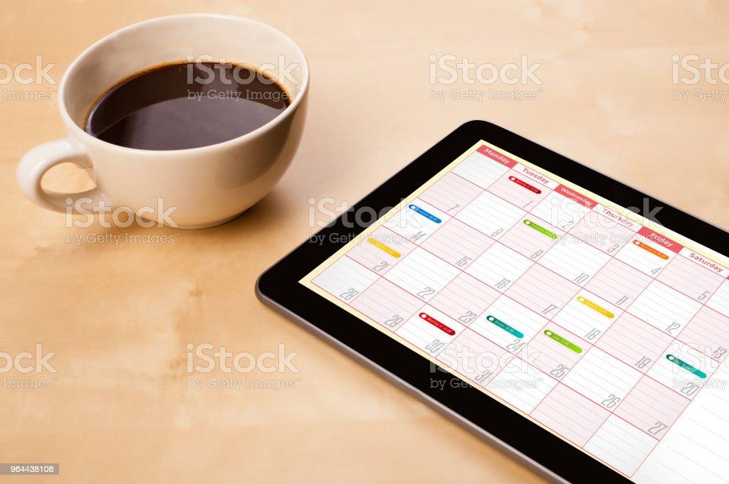 Mostrando o calendário na tela com uma xícara de café em uma mesa de pc da tabuleta - Foto de stock de Café - Bebida royalty-free