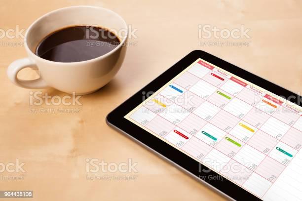 Foto de Mostrando O Calendário Na Tela Com Uma Xícara De Café Em Uma Mesa De Pc Da Tabuleta e mais fotos de stock de Café - Bebida