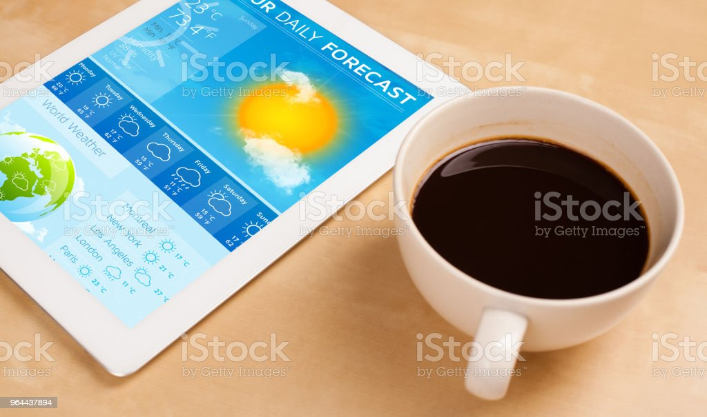 Tablet pc showing weather forecast on screen with a cup of coffee on a desk - Royalty-free Business Stock Photo