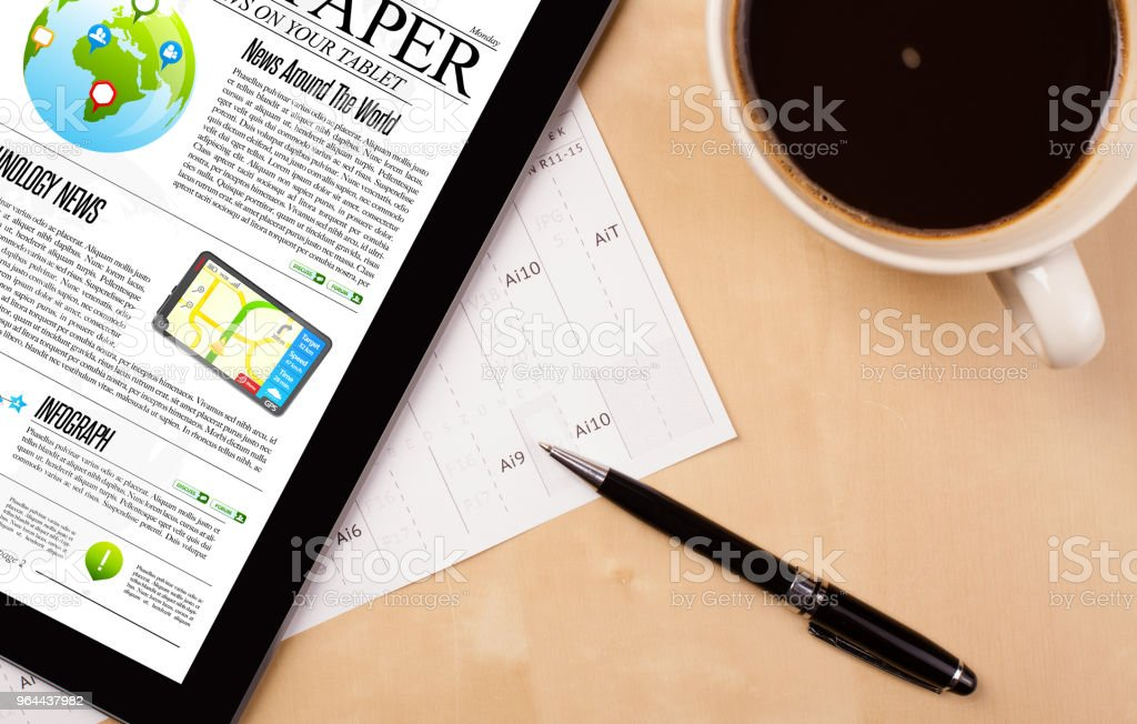 Tablet pc shows news on screen with a cup of coffee on a desk - Royalty-free Article Stock Photo