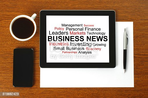 Tablet PC with business news, smart phone, paper, pen and cup of coffee on wooden background