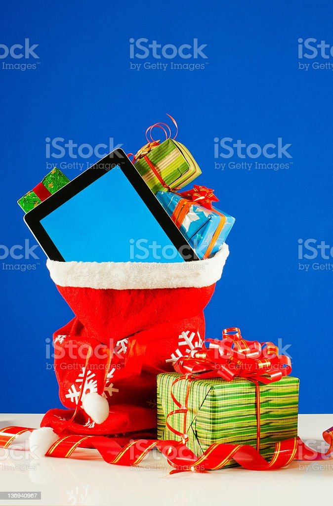 Tablet PC with heap of presents in red bag stock photo