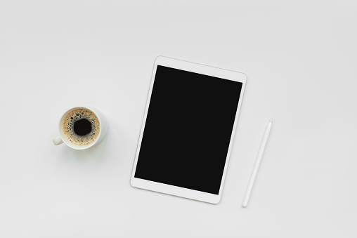Tablet, pencil and cup of coffee on white desk. Top view. Copy space. Mock-up