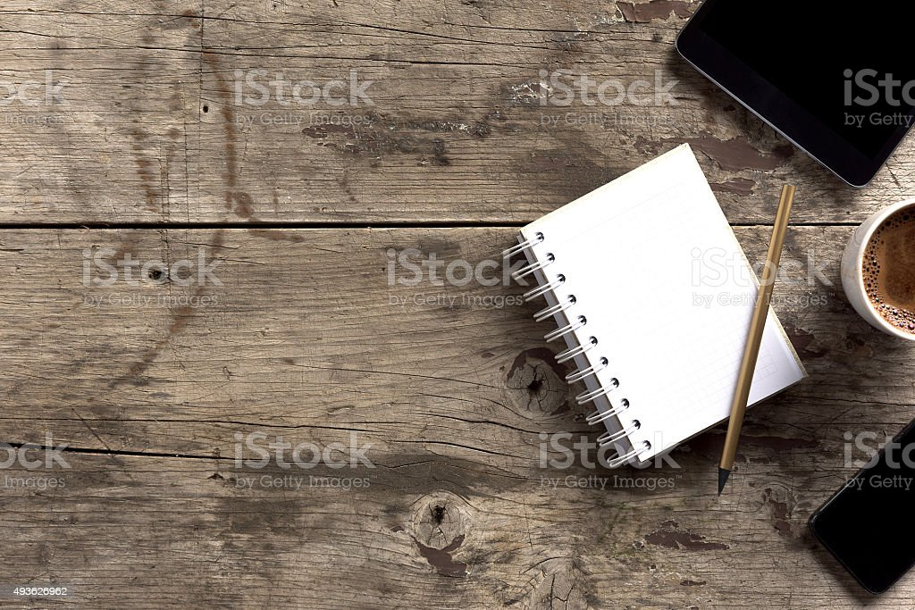 Tablet, phone, notepad and coffee on wooden table stock photo