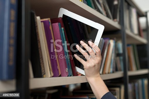 istock tablet picked with hand from book shelf in the library 499285056
