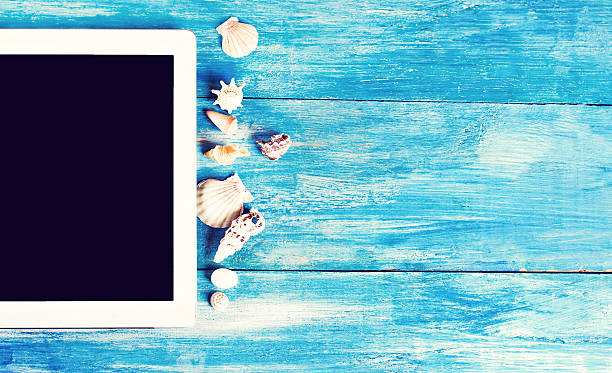 tablet, seashells, blue wood background - newspaper beach stockfoto's en -beelden