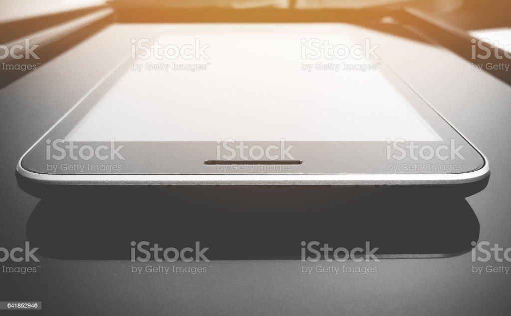 Tablet smart phone on office desk with light leak effect. stock photo