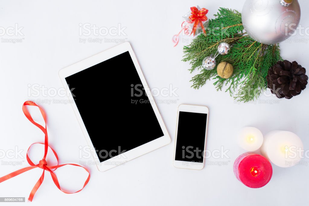 Tablet smartphone cell phone with christmas decoration, silver ribbon, branch of pane, silver snowflake, snow cone, new year stock photo