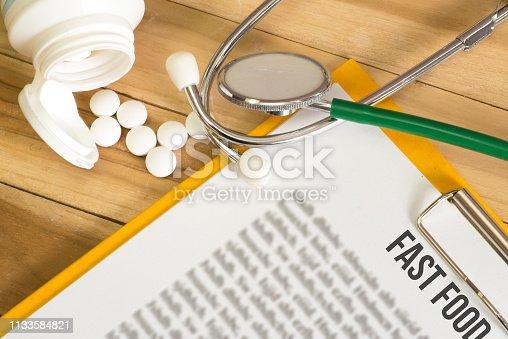 Tablette, Stethoskop und Warnung vor Fast Food