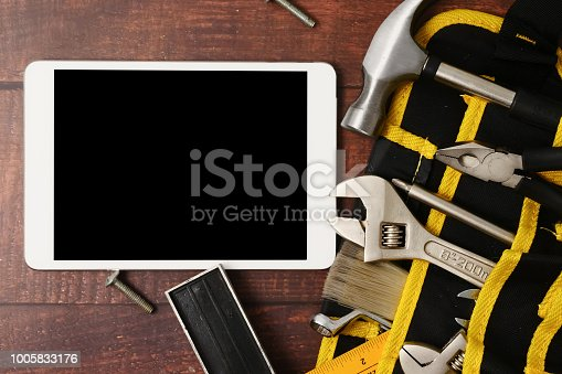 istock Tablet with blank screen, construction worker belt with tools on wooden table background 1005833176