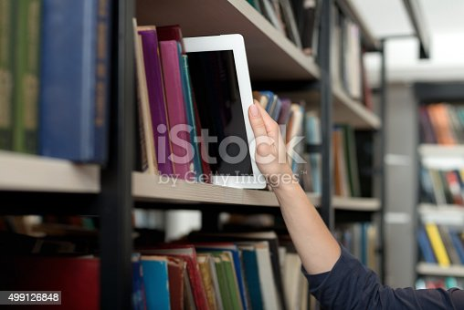 istock tablet with hand from book shelf in library 499126848