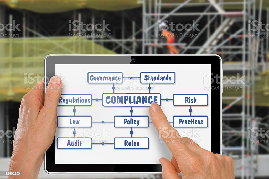 Tablet with Hands Researching Compliance Construction stock photo