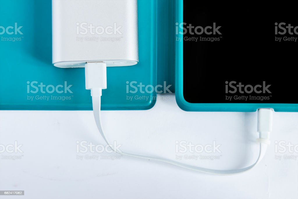 Tablet with portable external battery on white background royalty-free stock photo