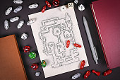 Tabletop role playing flat lay with RPG game dices, hand drawn dungeon map, rule books and pen on dark background