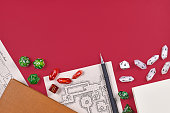 Tabletop role playing flat lay with RPG game dices, hand drawn dungeon map, rule books and pen at bottom of red background with empty copy space