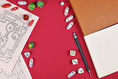 Tabletop role playing flat lay with RPG game dices, hand drawn dungeon map, rule books and pen on red background with empty copy space