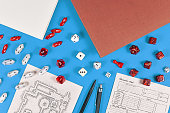 Tabletop role playing flat lay with RPG game dices, hand drawn dungeon map and character sheer, rule books and pen on blue background