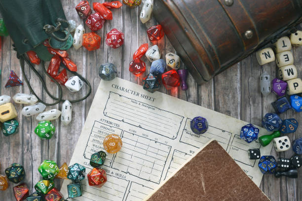 tabletop roleplaying flat lay with colorful rpg and game dices,  character sheet, rule book and treasure chest on wooden desk - ujęcie przedmiotu na stole zdjęcia i obrazy z banku zdjęć