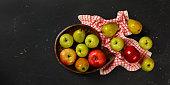 istock Tabletop view, wooden carved bowl with apples and pears, tablecloth, on black marble like board, space for text on left side 1161478480