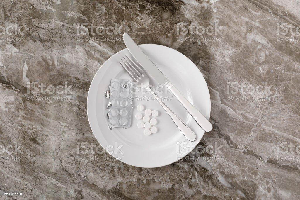 Tablets and empty blister pack on white plate on textured background with knife and fork foto stock royalty-free