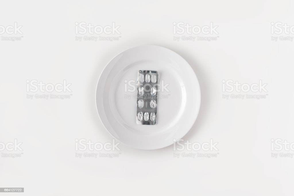 Tablets and empty blister pack on white plate on white background foto stock royalty-free