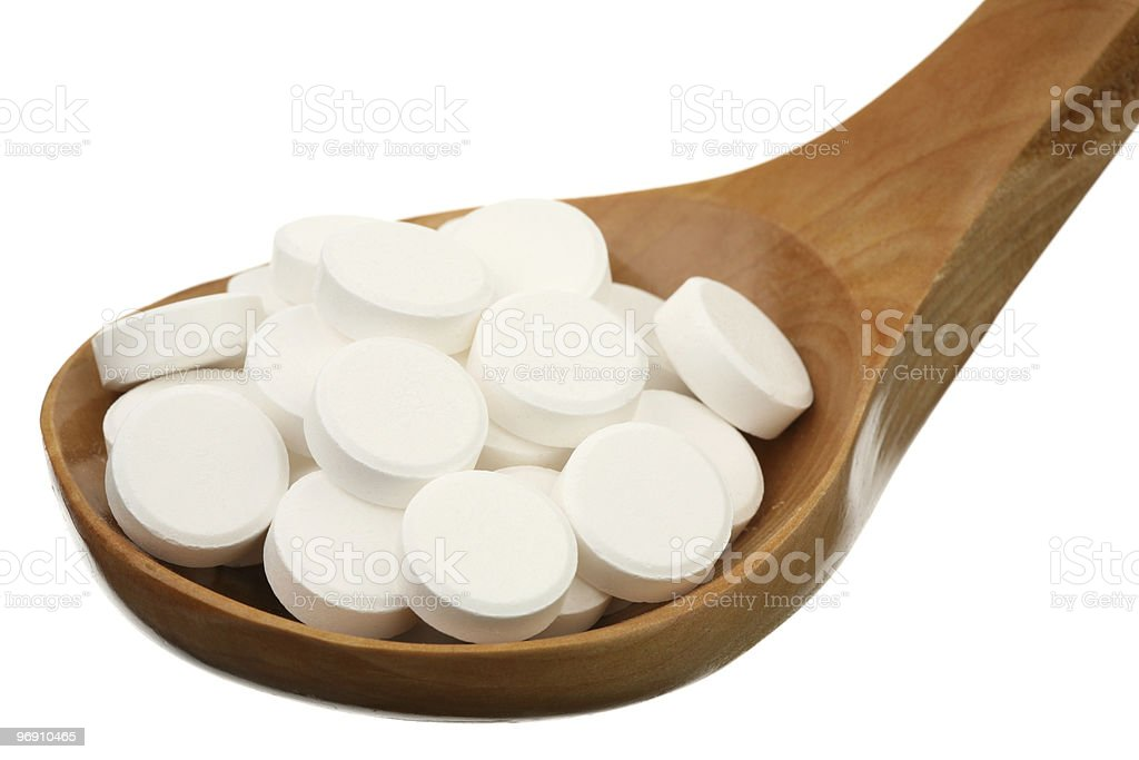 Tablets in a wooden spoon royalty-free stock photo