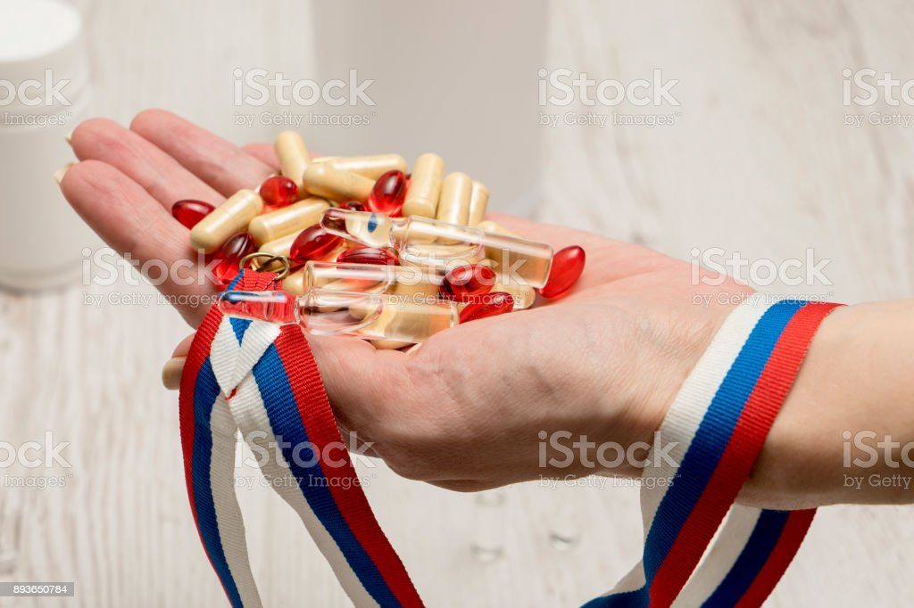 tablets, pills and syringe of doping drugs or medicine with russian tape flag in the hand after scandal at olimpic committee stock photo