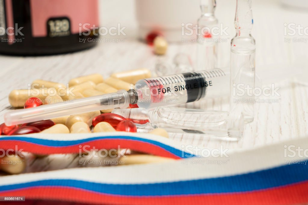 tablets, pills and syringe of doping drugs or medicine with russian tape flag on the table after scandal in olimpic committee stock photo