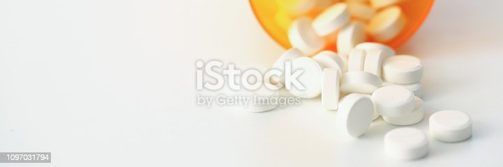 Tablets scattered white color jar on table of pharmaceutical laboratory pill for prescription and treatment various diseases chemistry background closeup