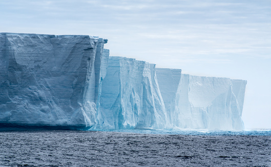 Massive flat topped iceberg floating in the Southern Ocean of Antarctica showing the weathered cracks and fissures on the sides