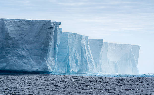Tabular iceberg in Antarctica   Massive flat topped iceberg floating in the Southern Ocean of Antarctica showing the weathered cracks and fissures on the sides  ice floe stock pictures, royalty-free photos & images