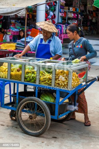Tachileik, Myanmar - December 13, 2011: Fruit vendors at a street market. The town is a popular destination for travellers making a visa run from Thailand, and Thai people looking for cheap goods from Myanmar.