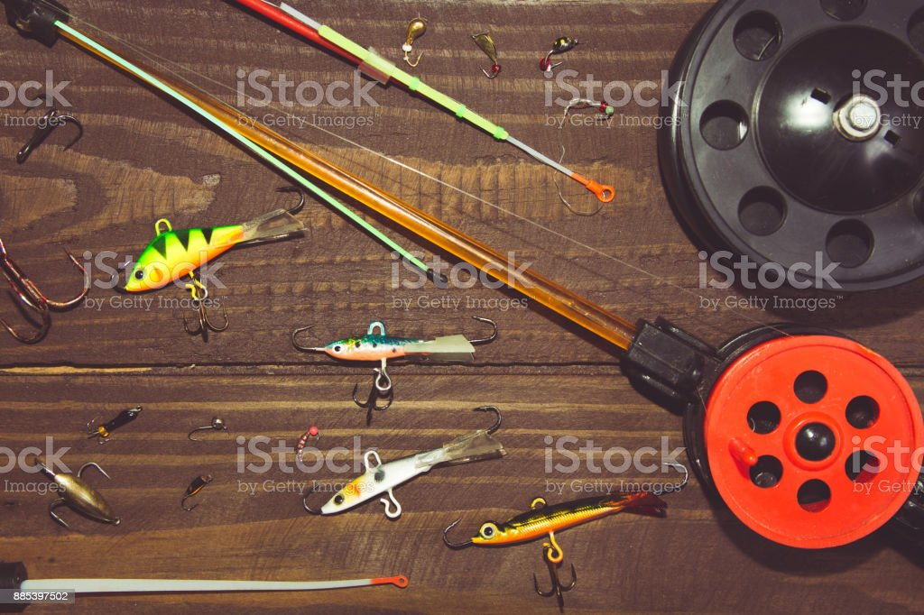 Tackle for winter fishing. Fishing rods and accessories on a wooden table. The view from the top. stock photo