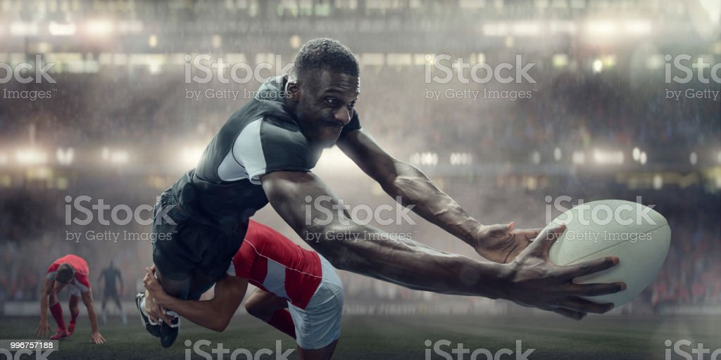 A black rugby player diving in mid air holding rugby ball...