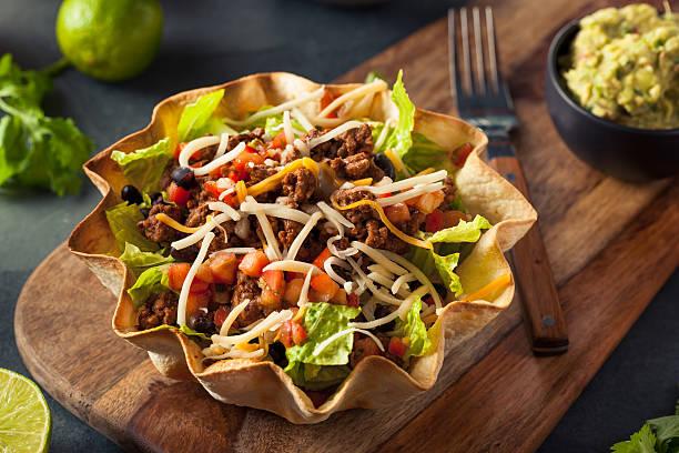 taco salade dans un bol de maïs - tacos photos et images de collection